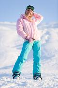 photo of cheerful young female in sporty clothes standing on snow and looking at - stock photo