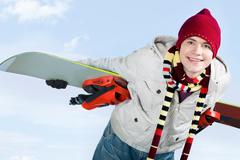 photo of skillful teenager with snowboard behind his back over blue background - stock photo