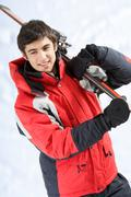 portrait of healthy man with pair of skis in hands looking aside and smiling - stock photo