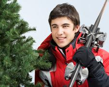 Stock Photo of portrait of happy male with skis in hand and fir tree near by
