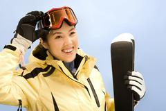 portrait of sport woman holding her skis and touching glasses - stock photo