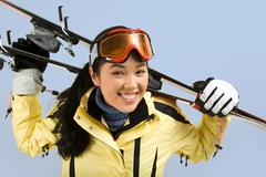 portrait of smiling girl with sport glasses holding the skis on her back - stock photo