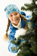 Portrait of young pretty woman peeping from christmas tree Stock Photos