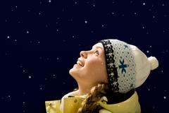 Portrait of amazed girl looking at falling snowflakes Stock Photos