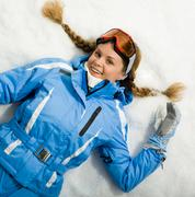 portrait of woman with skis resting on snow - stock photo