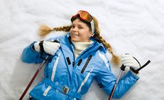 portrait of teenager holding skiing stick and lying on snow - stock photo