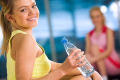 portrait of sporty girl with bottle of water looking at camera during physical t - stock photo