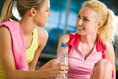 portrait of two pretty friends having a chat during workout in gym - stock photo