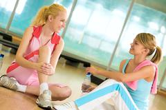 photo of two girls sitting on the floor of gym and having friendly talk - stock photo