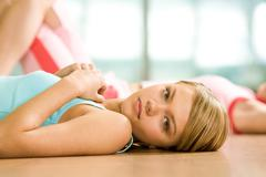pretty young girl lying on the floor during workout and looking at camera with c - stock photo