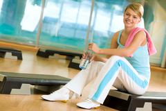 sporty female sitting in the gym with bottle of water in hands and smiling - stock photo