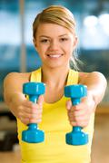 happy girl stretching her hands with blue dumbbells during workout - stock photo