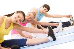 Portrait of young female doing stretching exercise among other people Stock Photos