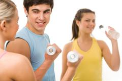 portrait of young male instructor interacting with girl during physical training - stock photo