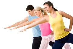 portrait of young sporty people doing physical exercise altogether - stock photo