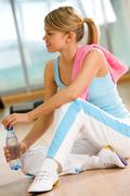 Healthy teenage girl sitting on the floor with bottle of water in hand Stock Photos