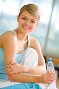 Portrait of lovely girl holding bottle of water in hand and smiling Stock Photos