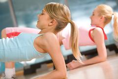 Image of sporty girl doing physical exercise on elbows Stock Photos