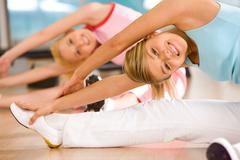 Image of sporty girl sitting on the floor and doing stretching exercise Stock Photos