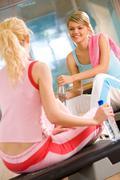 Kuva kahdesta teini-ikäistä tyttöä istuu urheilu kuntosali ja kommunikoi Kuvituskuvat