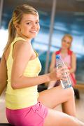 happy girl sitting on mat with bottle of water in hand and looking at camera wit - stock photo