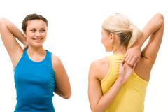 photo of two pretty friends having a chat during workout in gym - stock photo