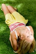 Photo of happy blond female lying on green grassland and looking at camera Stock Photos