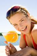 Photo of beautiful woman holding a orange cocktail and laughing Stock Photos