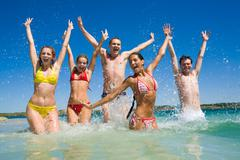 Image of happy teens playing in lake during their vacation Stock Photos