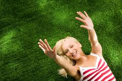above view of young glad female lying on green grassland and stretching her arms - stock photo