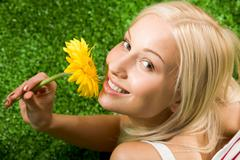 Close-up of cheerful young female with yellow beautiful flower in hands looking Stock Photos