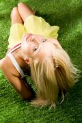 photo of young blond female lying on green grassland and looking at camera - stock photo
