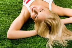 Photo of happy blond female lying on green grass and enjoying summer day Stock Photos
