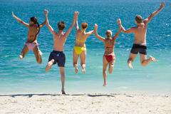 Portrait of five teens jumping into lake simultaneously holding each other by ha Stock Photos
