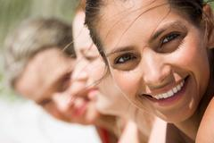 face of young woman looking at camera on hot summer day with her friends at back - stock photo