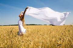 image of happy woman holding a white fabric in wheat meadow - stock photo