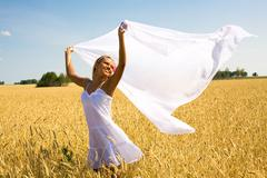 image of happy female with white fabric in wheat meadow - stock photo