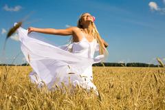 photo of glad girl with white fabric looking upwards in wheat meadow - stock photo