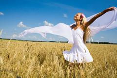 Photo of glad girl holding white chiffon shawl in wheat meadow and looking at sk Stock Photos