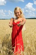 photo of pretty blonde in red dress standing in wheat field and stretching arms - stock photo