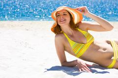 image of luxurious woman in bikini and hat relaxing on the seashore on hot day - stock photo