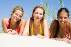 Portrait of group of girls lying on sand and looking at camera with smiles Stock Photos
