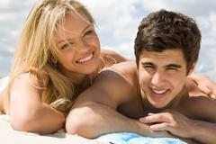 photo of smiling girl embracing her boyfriend while sunbathing on the beach - stock photo