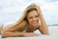 Image of female in white bikini lying on sandy beach and looking at camera Stock Photos