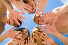Below angle of several teens keeping their hands in the form of circle with blue Stock Photos
