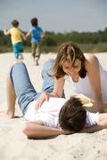 Image of amorous couple lying on sandy beach with their sons at background Stock Photos