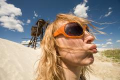 Portrait of young female in sunglasses protruding her lips on background of beac Stock Photos
