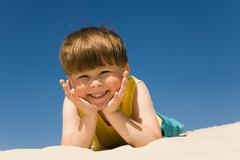 happy boy lying on sand and looking at camera with smile on hot summer day - stock photo