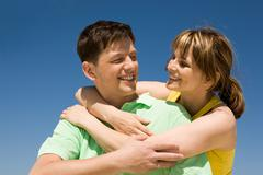 Stock Photo of photo of happy woman embracing her husband against bright blue sky