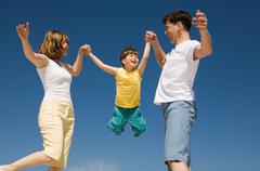 Photo of happy parents holding their son by hands in jump with bright blue sky a Stock Photos